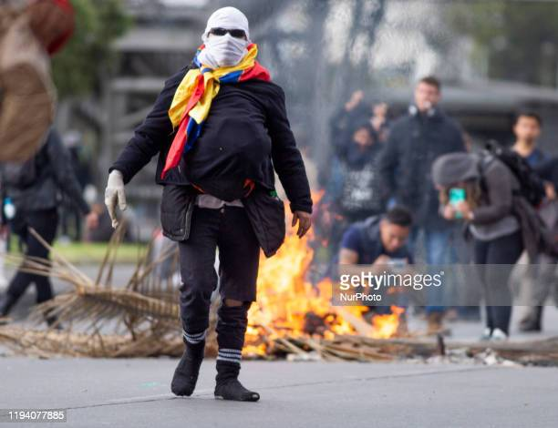 A hooded man wears a Colombian flag in the riots supporting the national strike that has been in Colombia for 4 months on January 16 2020 in Bogota...