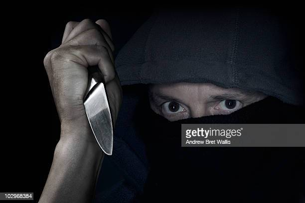 hooded masked man holding knife in his raised hand - andrew dieb stock-fotos und bilder