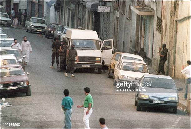 Hooded military forces stand in front of the Islamic Salvation Front headquarters in Algiers 30 June 1991 prior the arrest of the leader of the...