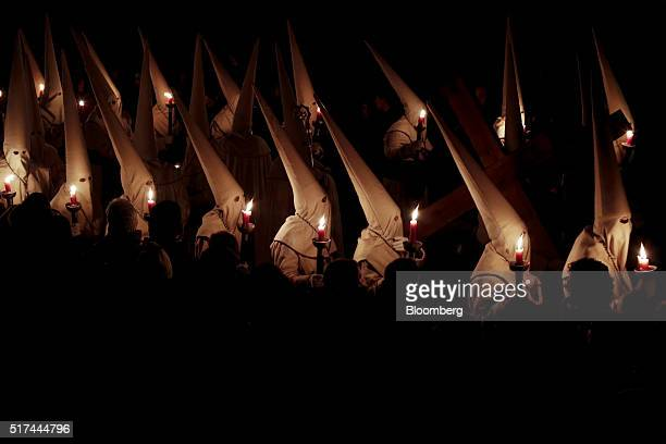 Hooded penitents from the Brotherhood of Jesus Lying hold candles whilst taking part in a procession during Holy Week celebrations in Zamora, Spain,...