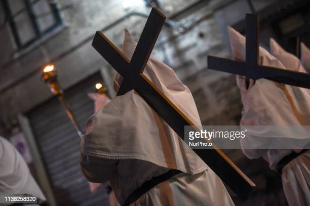 Hooded Penitents of the Arciconfraternita of Saint Monica carry crosses and torches as they take part in Good Friday procession long the streets of...