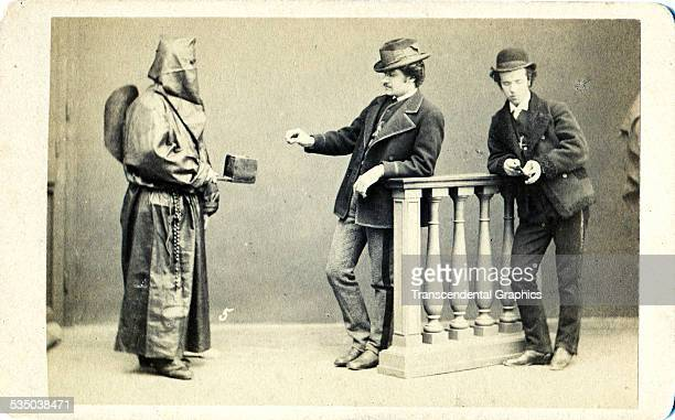 A hooded representative of a Catholic brotherhood asks for donations in his metal box from Rome Italy around 1860