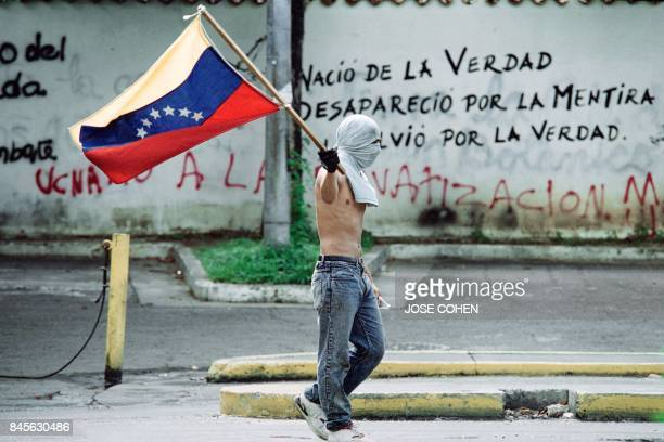 A hooded student carries the Venezuelan flag near the Central University of Caracas on June 11 1992 during a demonstration against the government of...