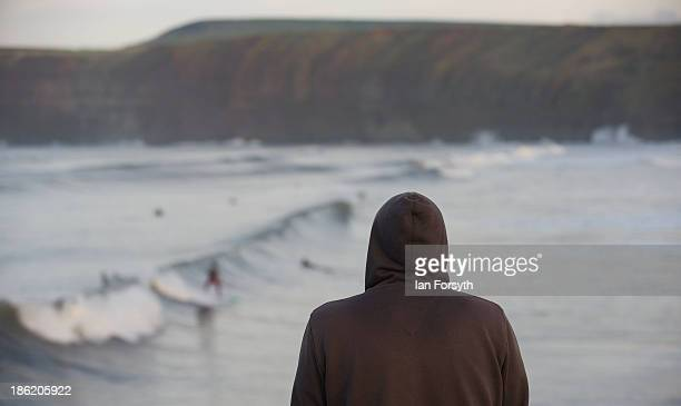 A hooded surfer stands on the pier and looks out over the surf on October 21 2013 in Saltburn United Kingdom The surfing scene on the north east...