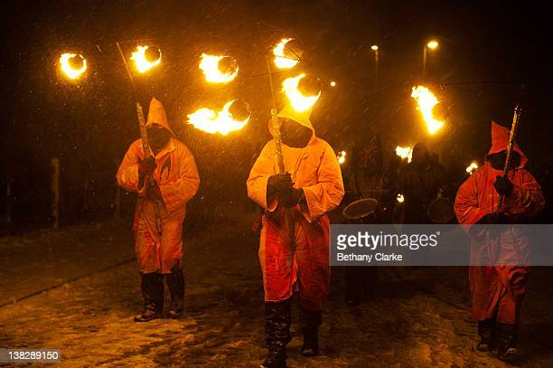 Hooded torch bearers lead the winter procession through the snow on February 4 2012 in Huddersfield England Imbolc is a pagan festival that marks the...