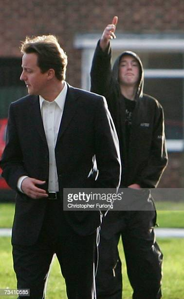 'Hoodie' Ryan Florence aged 17 gestures a pretend 'clickbang' shooting at Tory leader David Cameron as he tours the Benchill Estate on 22 February...