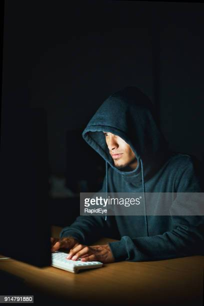 hoodie-wearing young man working late on computer, possibly a hacker - ominous stock pictures, royalty-free photos & images