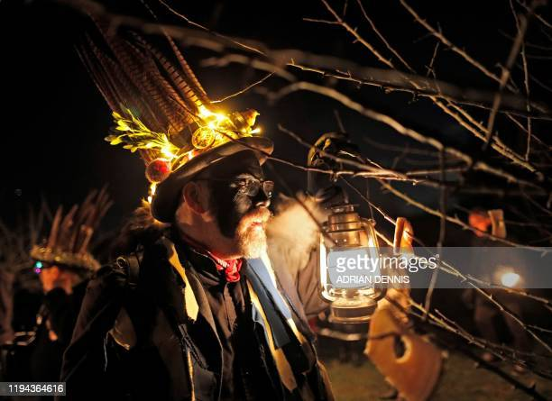 Hook Eagle Morris Man places a piece of toast on an apple tree branch during the annual Wassail night in Hartley Wintney, 40 miles west of London on...