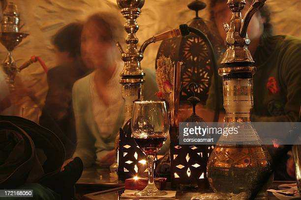 Hookah pipes next to glass of red wine and lanterns