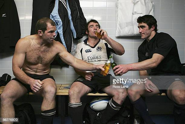 Hooker Anton Oliver of New Zealand shares a beer with Kelly Brown of Scotland and team mate and fellow hooker Andrew Hore following the All Black...