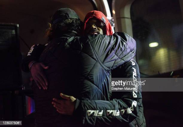 Hooker embraces another protester after a vigil for Dolal Idd, who was shot and killed by Minneapolis Police last night, on December 31, 2020 in...