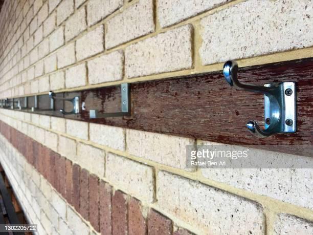 hooks hanged on a brick wall - rafael ben ari - fotografias e filmes do acervo