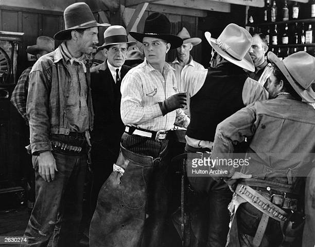 Hoot Gibson joins the other cowboys at the bar in a scene from the film 'Points West' directed by Arthur Rosson for Universal