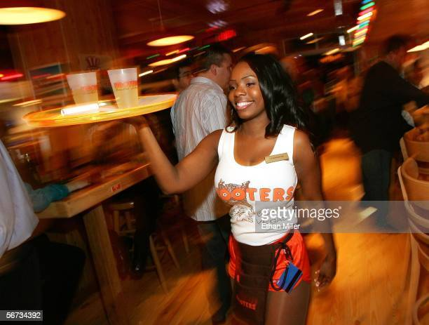 Hooters Girl Charmaine Fobbs carries drinks at the Hooters Restaurant during the grand opening of the Hooters Casino Hotel February 2, 2006 in Las...