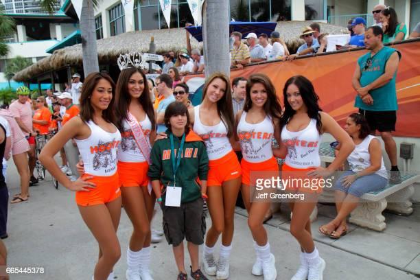 Hooters Girls posing with a boy at the deep sea fishing tournament at Miami Beach Marina