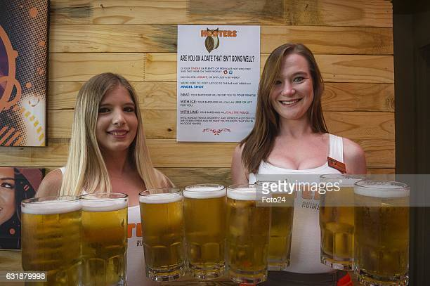 Hooters Girls; Yana Aerts and Hailey Sprenger hold beers in front of the Angel shot poster at Hooters Restaurant on January 16, 2017 in Johannesburg,...