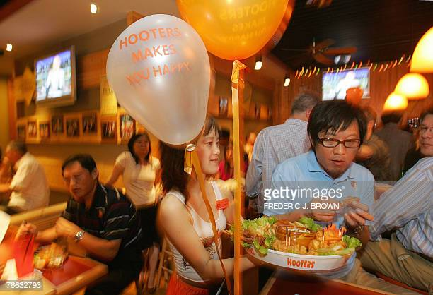 A Hooters waitress serves customers at the opening of the US restaurant chain's first outlet in Beijing 10 September 2007 and fourth overall in China...
