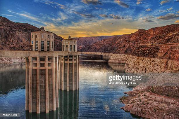 hoover dam by rock formation against sky - hoover dam stock photos and pictures