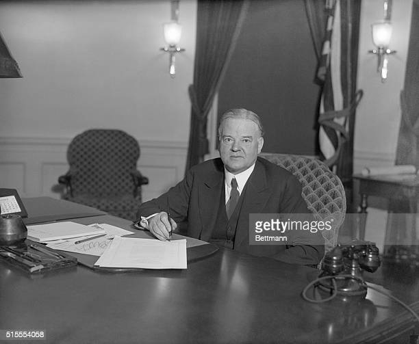 Hoover signs unemployment relief billPresident Hoover shown at his desk in the White House signing the bills passed by Congress authorizing...