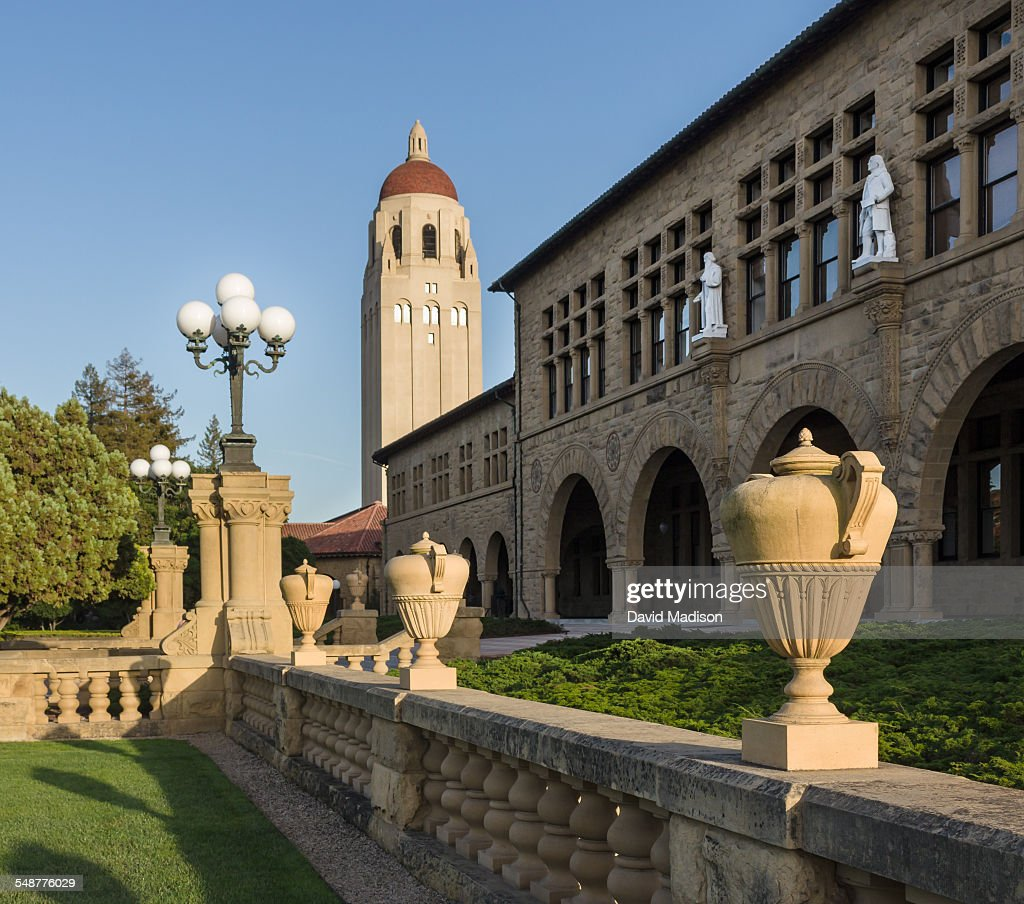 Hoover Tower rises above a building of the Main Quadrangle at Stanford University in Palo Alto, California, USA. Statues of Alexander von Humboldt and Louis Agassiz adorn the facade of Jordan Hall.