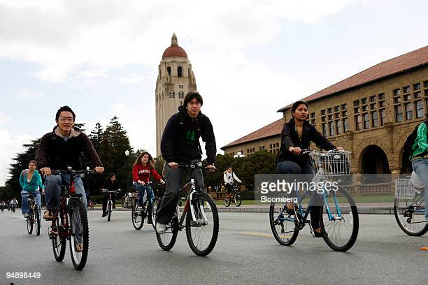 Hoover Tower stands beyond students riding bicycles through the Stanford University campus in Palo Alto California US on Wednesday Feb 20 2008...