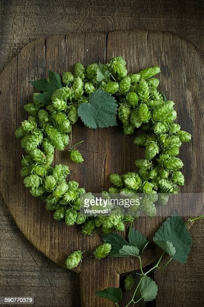 Hop wreath on wooden shovel and dark wood
