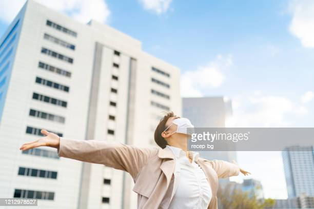 hope for life without coronavirus concept. businesswoman with protective facial mask outstretching her arms while looking up - free stock pictures, royalty-free photos & images