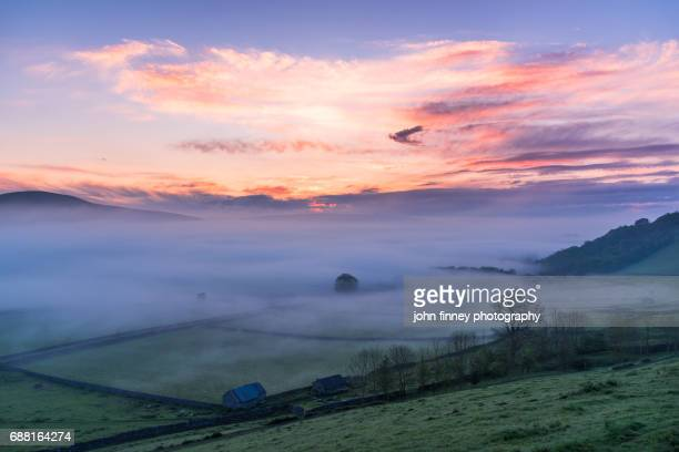 Hope valley covered in mist at dawn with a pink sky. English Peak District. UK.