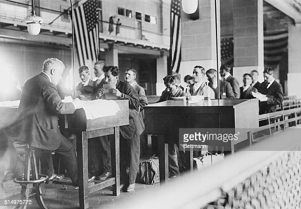Hopeful immigrants to the United States stand in line before an immigration official at Ellis Island May 27 1920