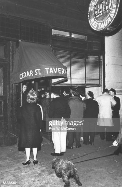 Hopeful patrons stand on the sidewalk in front of the Cedar Street Tavern and peer through the windows into the crowded nightspot New York New York...
