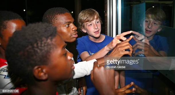 Hopeful student soccer players with friends and family view a list of those who made the freshman and junior varsity teams on the front window of...