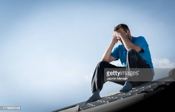 hopeless man feeling alone and lost sitting on top of roof - erectile dysfunction stock pictures, royalty-free photos & images