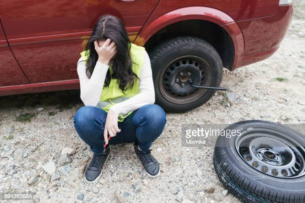 hopeless woman trying to change car tire - flat tire stock pictures, royalty-free photos & images