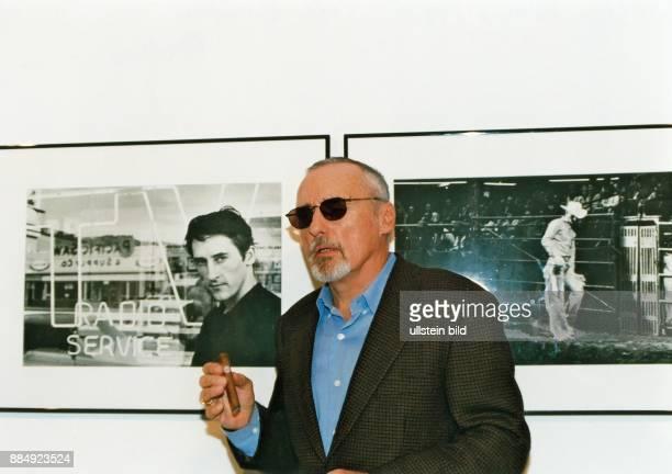 Hopper Dennis * Schauspieler Regisseur Fotograf USA Portrait mit Sonnenbrille und Zigarre vor Fotografien im Berliner Café 'Einstein'
