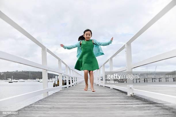 Hopping little girl in the green dress