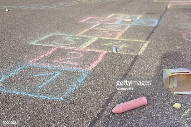 Hopscotch drawing with coloured crayon on asphalt