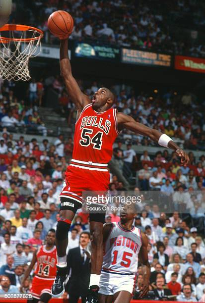 Horace Grant of the Chicago Bulls goes up to slam dunk the ball in front of Vinnie Johnson of the Detroit Piston during an NBA basketball game circa...