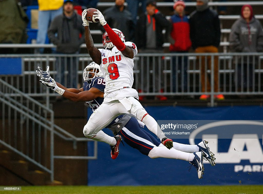 Horace Richardson #9 of the SMU Mustangs intercepts a pass in front of Geremy Davis #85 of the Connecticut Huskies in the second quarter during the game at Rentschler Field on December 6, 2014 in East Hartford, Connecticut.