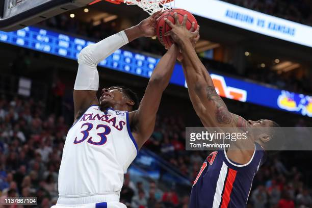 Horace Spencer of the Auburn Tigers fight for possession with David McCormack of the Kansas Jayhawks during their game in the Second Round of the...