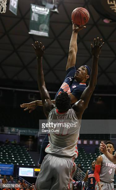 Horace Spencer of the Auburn Tigers shoots over Obij Aget of the New Mexico Lobos at the Stan Sheriff Center during the Diamond Head Classic on...
