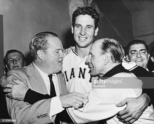 """Horace Stoneham owner of the miracle"""" club, and New York Giant's manager Leo Durocher hug Bobby Thomson in the dressing room after the Giants' third..."""