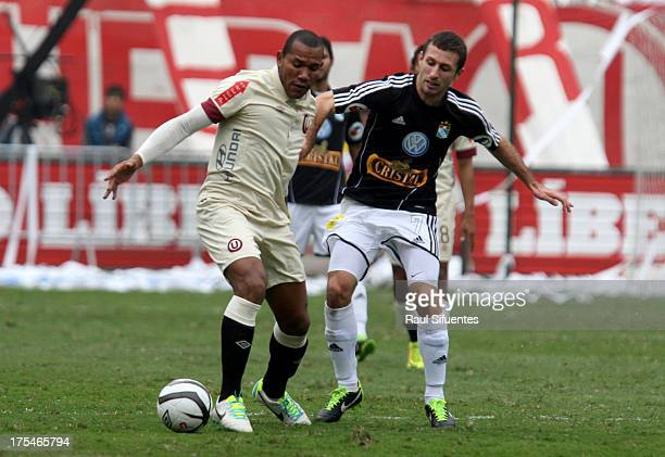 Horacio Calcaterra of Sporting Cristal fights for the ball with Jhon Galliquio of Universitario during a match between Universitario and Sporting...