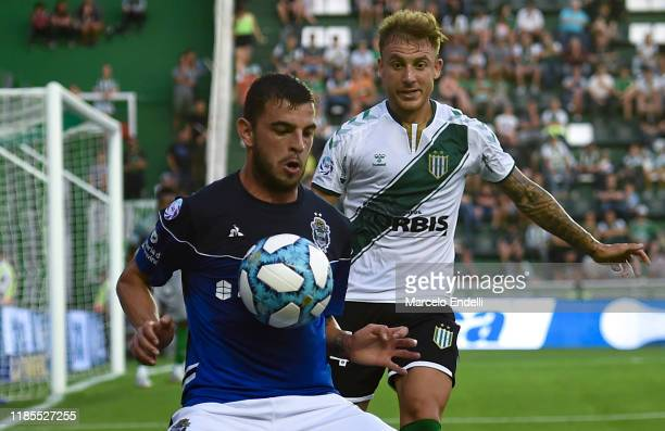 Horacio Tijanovich of Gimnasia y Esgrima La Plata fights for the ball with Rodrigo Arciero of Banfield during a match between Banfield and Gimnasia y...