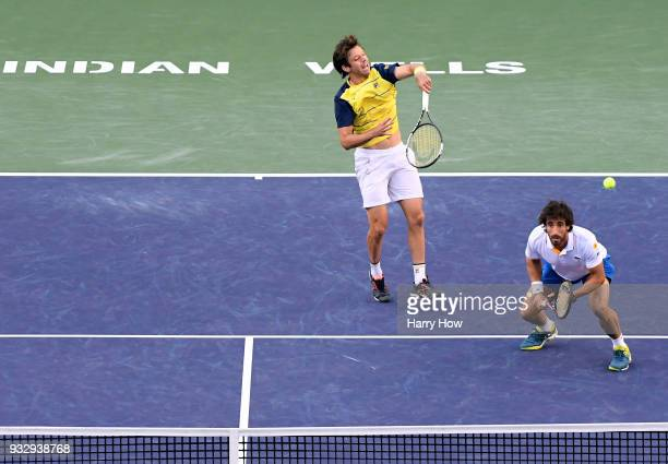 Horacio Zeballos of Argentina hits an overhead in front of partner Pablo Cuevas of Uruguay in their semifinal loss to Bob Bryan and Mike Bryan of the...
