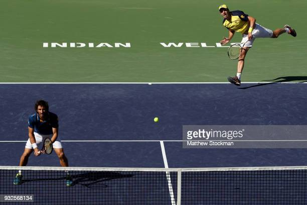 Horacio Zeballos of Argentina serves to Gilles Muller of Luxemburg and Sam Querrey while playing with Pablo Cuevas of Uraguay during the BNP Paribas...