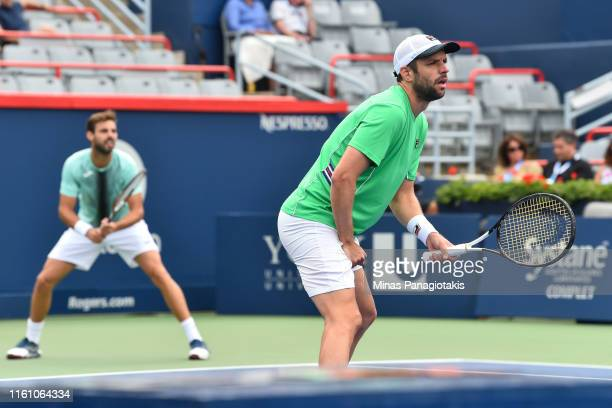 Horacio Zeballos of Argentina take position near the net as teammate Marcel Granollers of Spain prepares to receive a serve during the mens doubles...