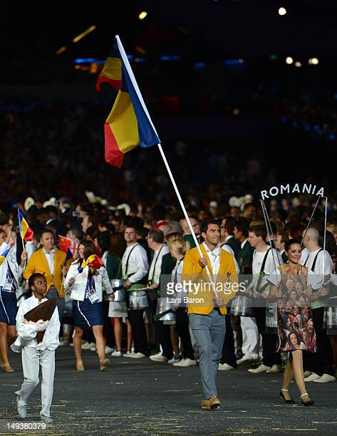 Horia Tecau of the Romania Olympic tennis team carries his country's flag during the Opening Ceremony of the London 2012 Olympic Games at the Olympic...