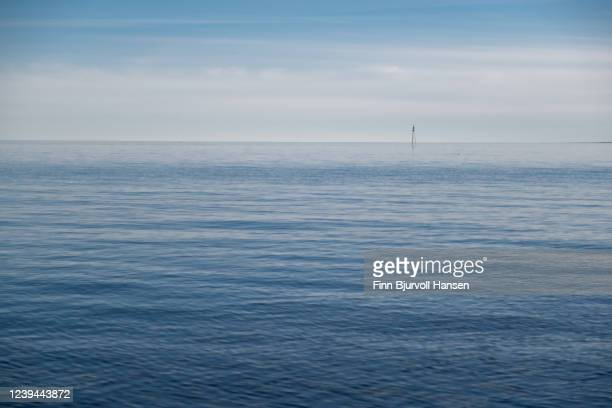 horizon over the sea, small lightbuoi in the background - finn bjurvoll stock pictures, royalty-free photos & images