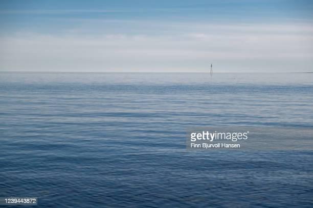 horizon over the sea, small lightbuoi in the background - finn bjurvoll ストックフォトと画像