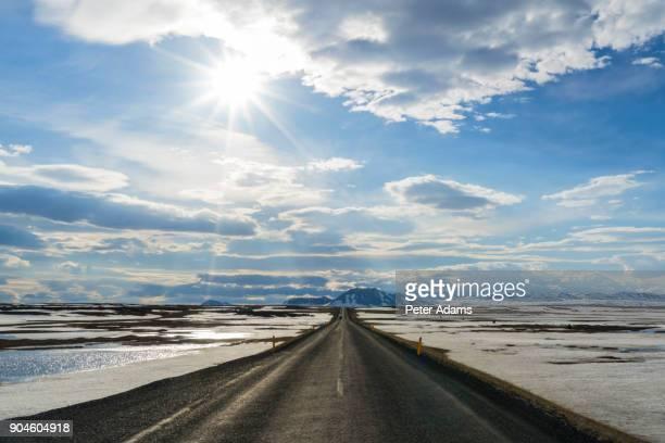 horizon road in snowy landscape nr lake myvatn, iceland - パース ストックフォトと画像